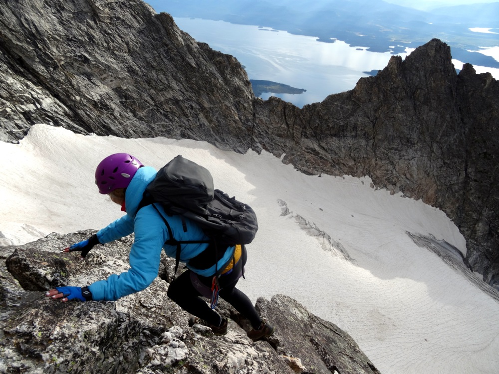 Bree scrambles around to the first of many rappels on the CMC route with the Falling Ice Glacier far below her.