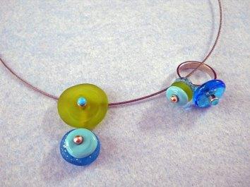 Marlein Bong, setje van hanger met ring; hanger aan edelstalen kabel. Materialen: zilver, zelfgemaakte glazen schijven en chrysopraas in zilver gezet.