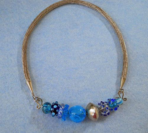 Marlein Bong, Handgepunnikte ketting van zilver met afkoppelbaar tussenstuk met zelfgemaakte kralen in blauwtinten.