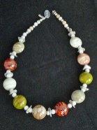 """Nicoline Lenskens, """"Roisin"""", geregen collier van glaskralen in natuurtinten, met natuursteentjes, zilveren kraaltjes en gekronkelde zilveren schijfjes; lengte collier 43 cm."""