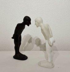 Pas de deux, twee staande mannen figuren 1x zwart en 1x wit.