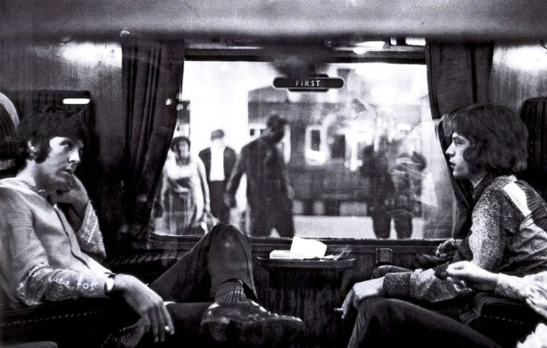 Paul McCartney and Mick Jagger sit opposite each other on a train to Bangor (1967)