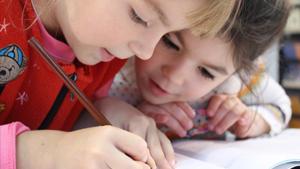 gros plan sur deux enfants qui écrivent à l'école