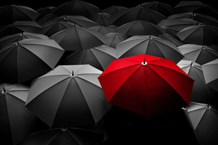 red umbrella in a sea of black umbrellas