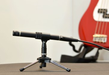 Placing an ambient mic at the front of the stage on a low mic stand minimizes its visual impact.