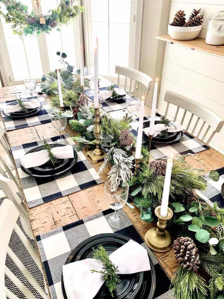 plaid black and white christmas table setting with greenery and pine cones