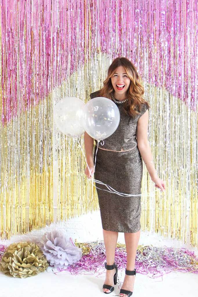 girl standing with balloon in front of chevron foil party backdrop