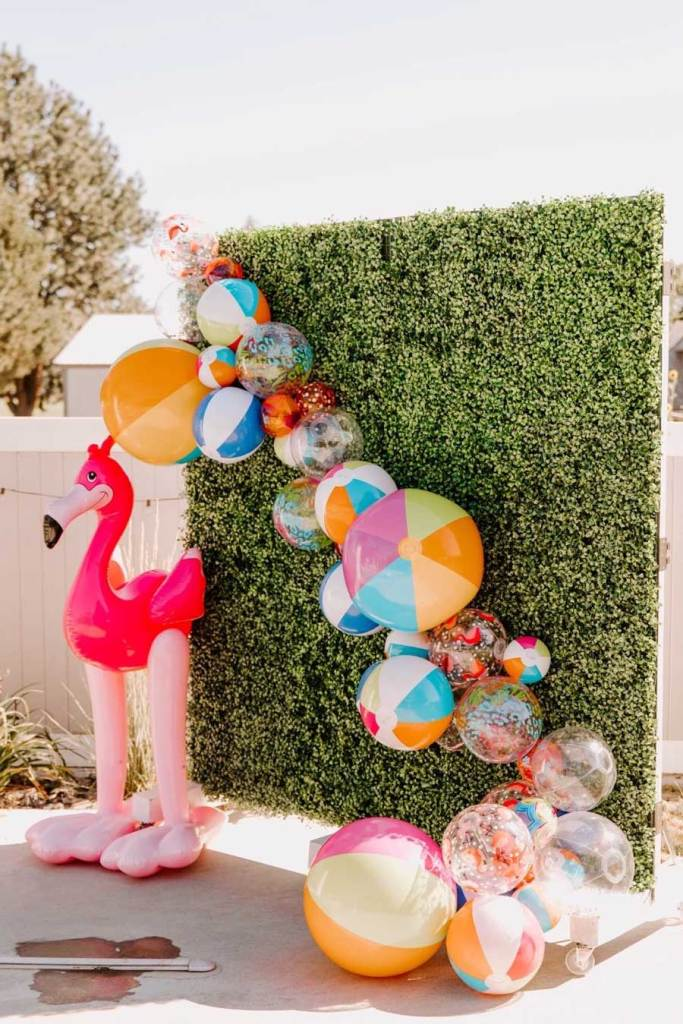 Inflatable beachballs hanging on grass wall photo backdrop