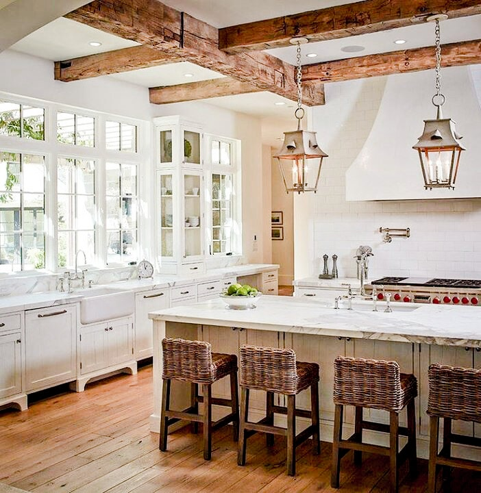 Country fresh chic modern farmhouse kitchen with large timber beams and lots of light in the large windows