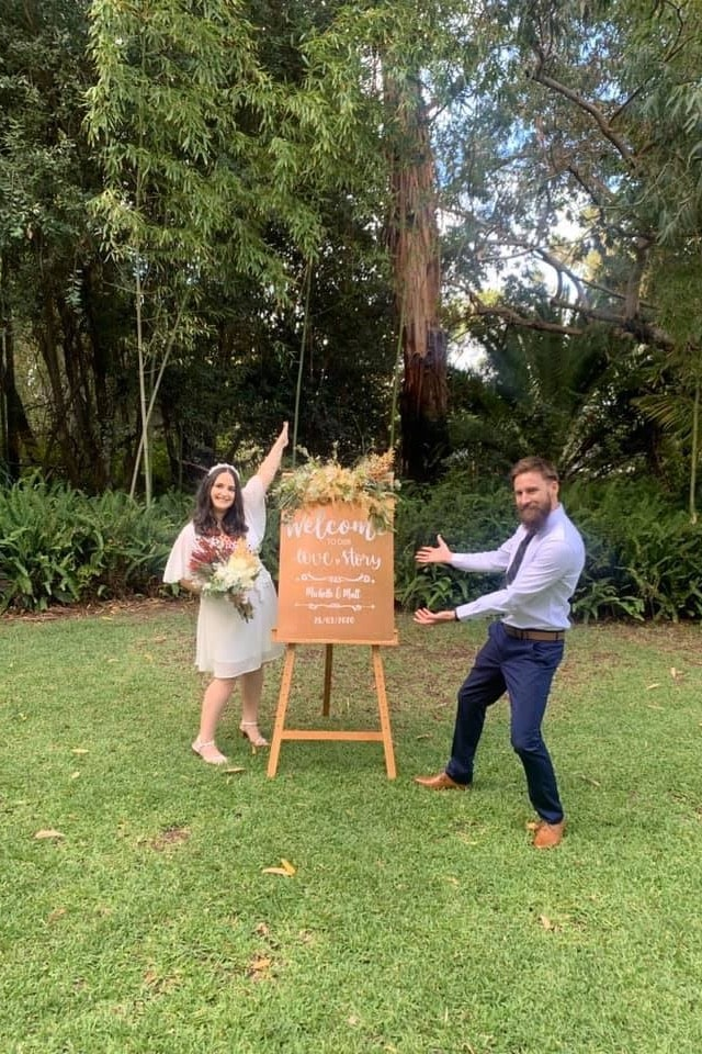 newly married couple standing in front of wedding sign