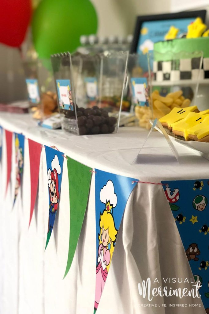 Strung paper bunting in Super Mario characters wrapped around party table