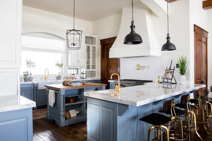 Modern blue farmhouse kitchen with a touch of rustic including marble benchtops, brass fixtures and huge range