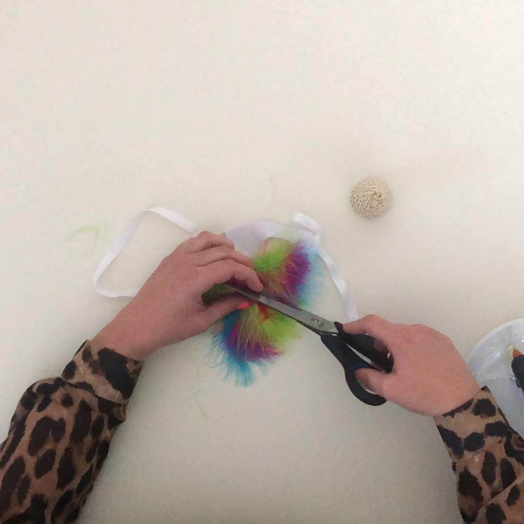 cutting feather trim from cat hat
