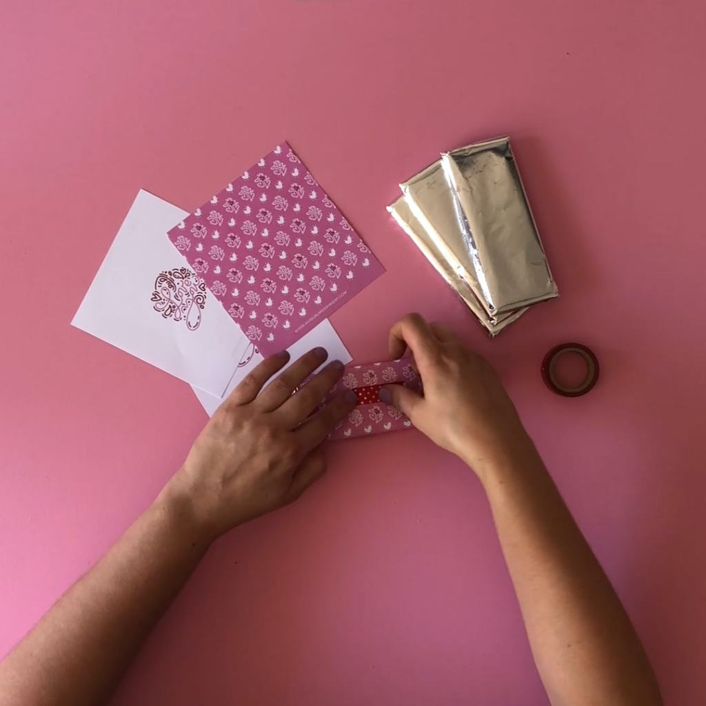 Tape down paper chocolate bar wrapper to secure