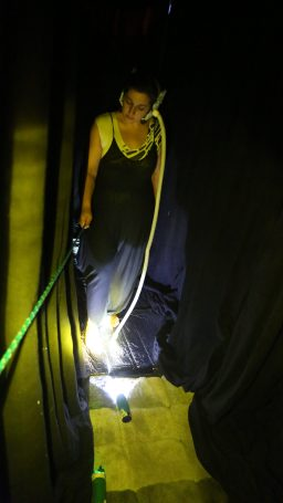 'Listening with the soles of your feet'. This space is completely dark and the pathway is covered with materials of different textures (bubblewrap, cardboard, sheepskin, cellophane etc). The tube earmuffs allow you to hear the hidden sounds of the surfaces as you feel them with your feet