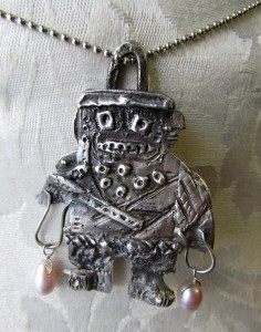 A picture of a handmade silver robot pendant with pearls