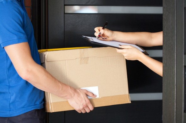 Delivery guy holding package while woman is signing documents.jpeg