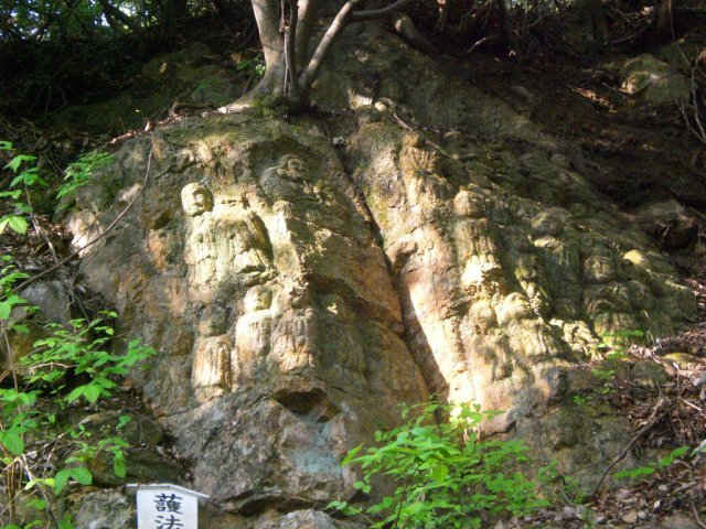 Ancient stone statues carved into the hillside