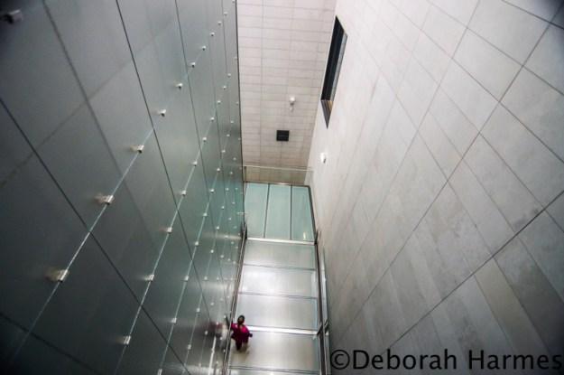 Taken from a high walkway overhead, a lone woman walks on a green-tinted glass bridge within the contemporary interior of the NGV art museum in Melbourne, Australia.