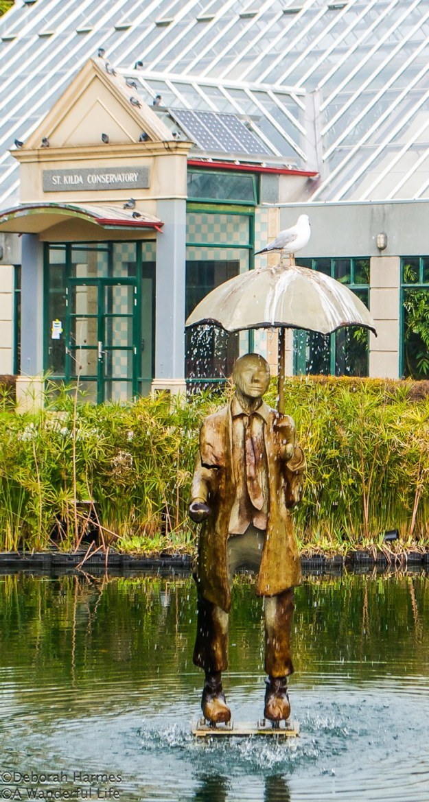 Charming metal sculpture 'walking on water' with a seagull perched on his umbrella