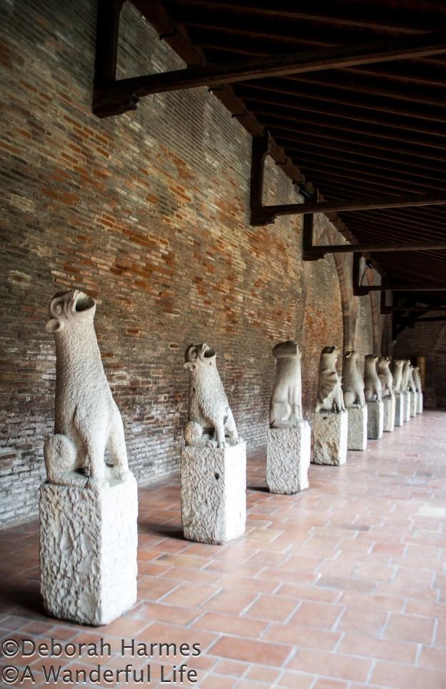 Historic gargoyles on display along the cloister walk.
