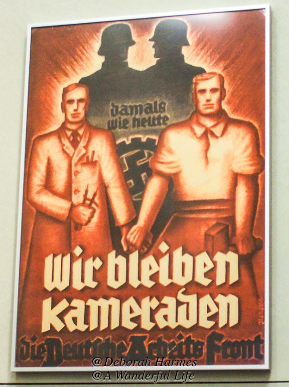 Whether you are a university educated man who works with his brain or a tradesman who works with his hands, the we're-all-in-this-together approach is on display in this propaganda poster.