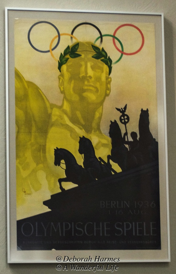 Silhouette of the top of the iconic Brandenburg Gate in Berlin overlaid onto this poster for the summer Olympics.