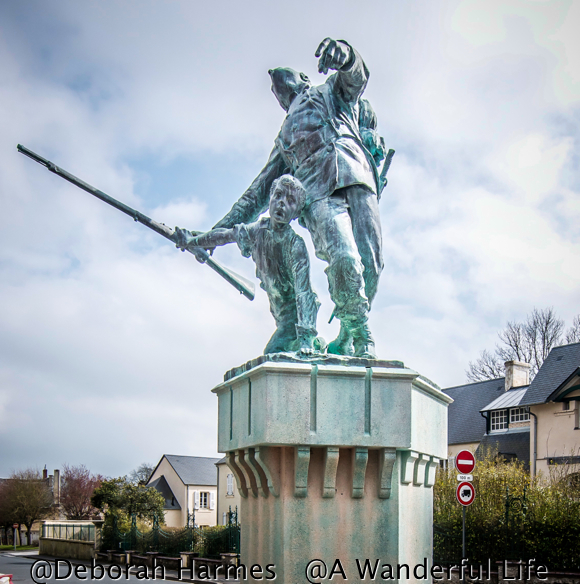 A poignant war memorial on a side street in Bayeux, Normandy, France. As a French soldier is shot and begins to fall, the young boy takes the weapon and will carry on.