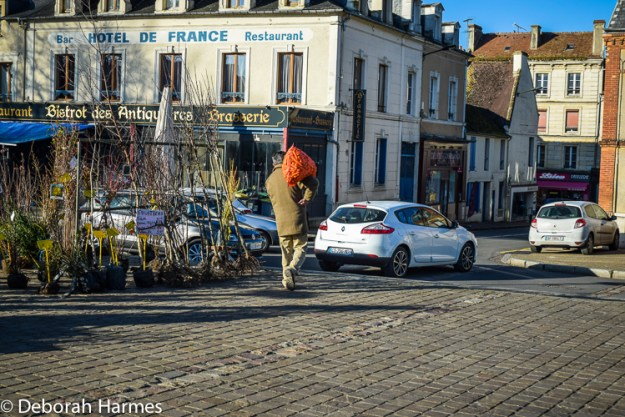 Carrot sack toting man at weekly market in rural Normandy.