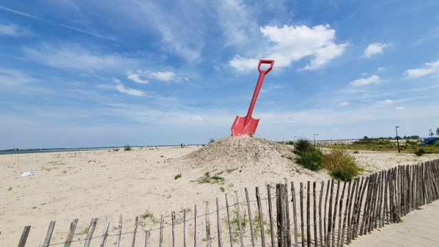 Large shovel on mound of sand indicating where the beach is