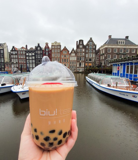 Biu! Tea cup in front of Amsterdam canal houses on Damrak