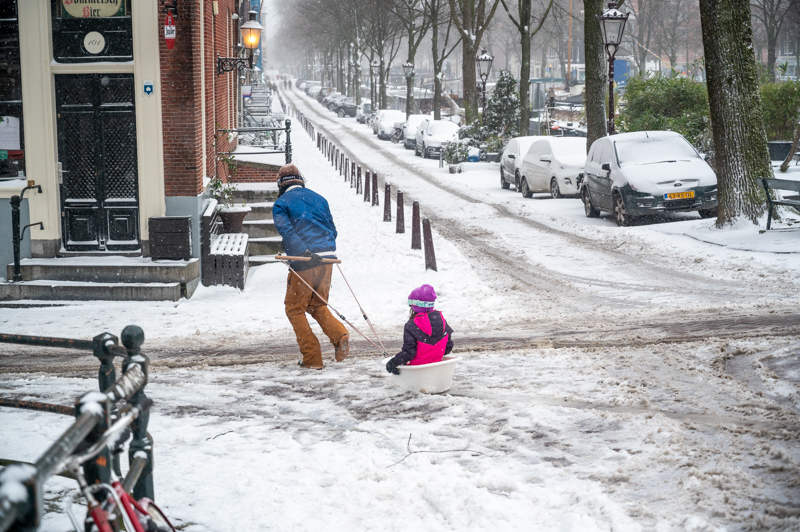 Father pulling his daughter on a sled through Amsterdam