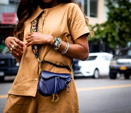 How to style the new Dior saddle bag and logo strap. Atlanta fashion and lifestyle blogger Monica Awe-Etuk wearing utility jumpsuit by FIA Factory, Chloe heart sunglasses, the new Dior Saddle bag, with logo strap, and white cult gaia mules