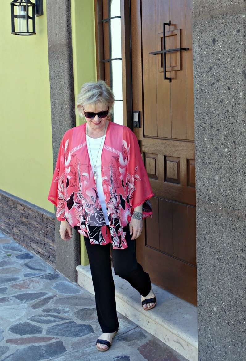 Jennifer of A Well Styled Life wearing black pants, white tank and coral ruana in Mexico