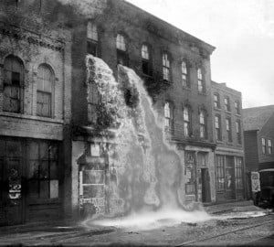 Illegal alcohol, discovered by Prohibition agents, pours out of a storefront in Detroit. Photo courtesy of Wayne State University's Reuther Library.