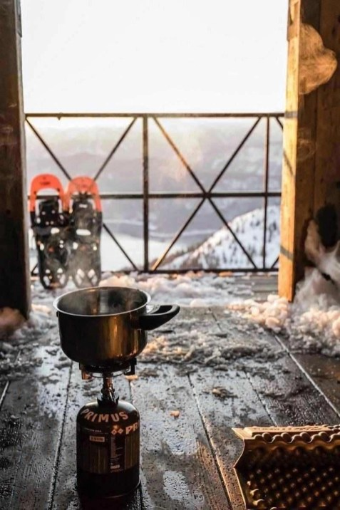Boiling water in a mountain hut surrounded by snow