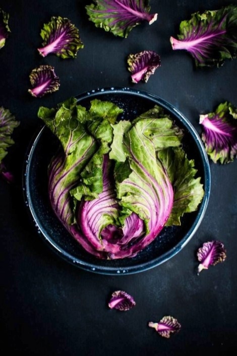 purple and green lettuce leaves on a dark plate - eating without gluten while traveling