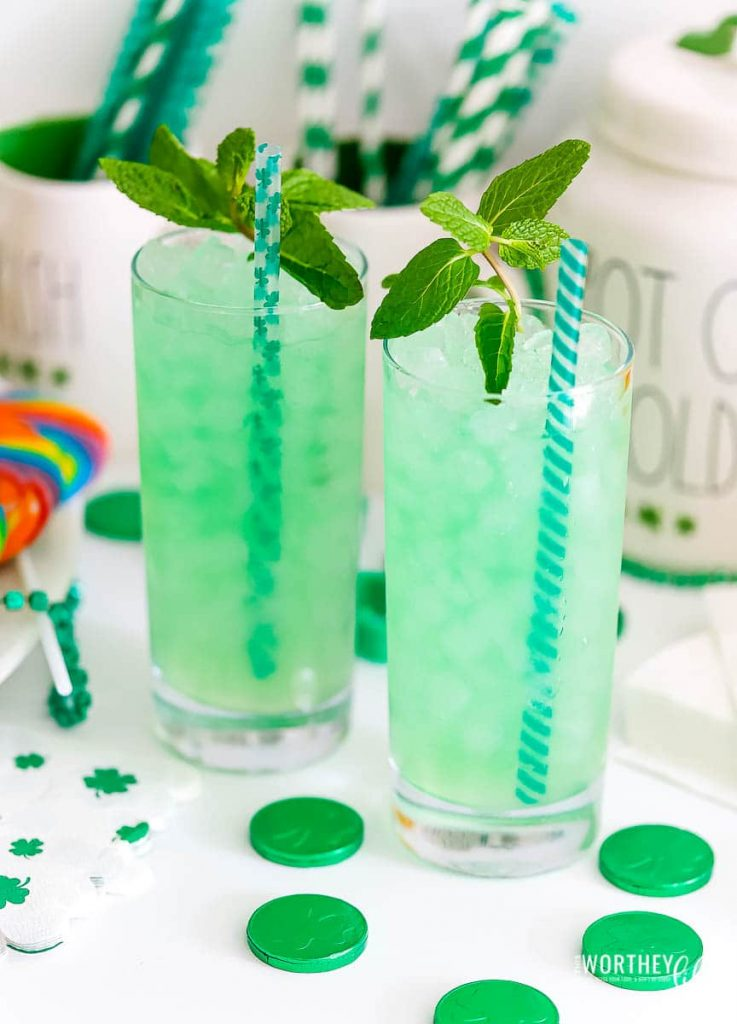 two tall glasses filled with green drink and mint