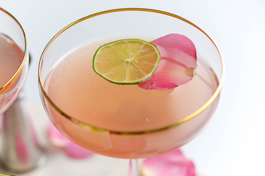 close up of a gold rimmed glass filled with a pink vodka cocktail