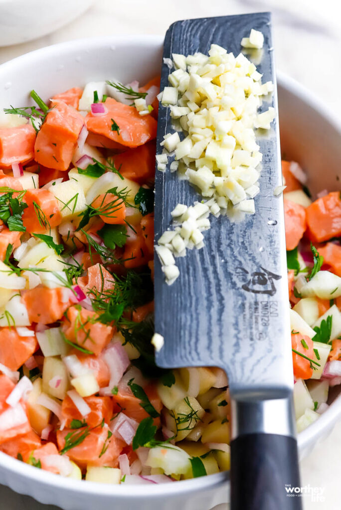 a white mixing bowl filled prepared ceviche and garlic