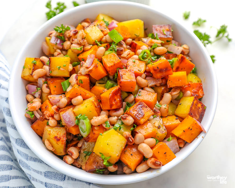 a white bowl filled with sweet potato and black eyed peas hash
