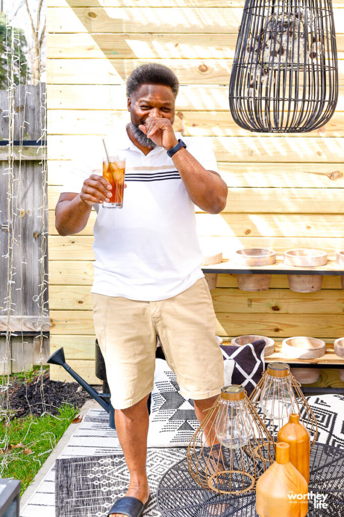 a man standing with a glass of ice tea in his hand