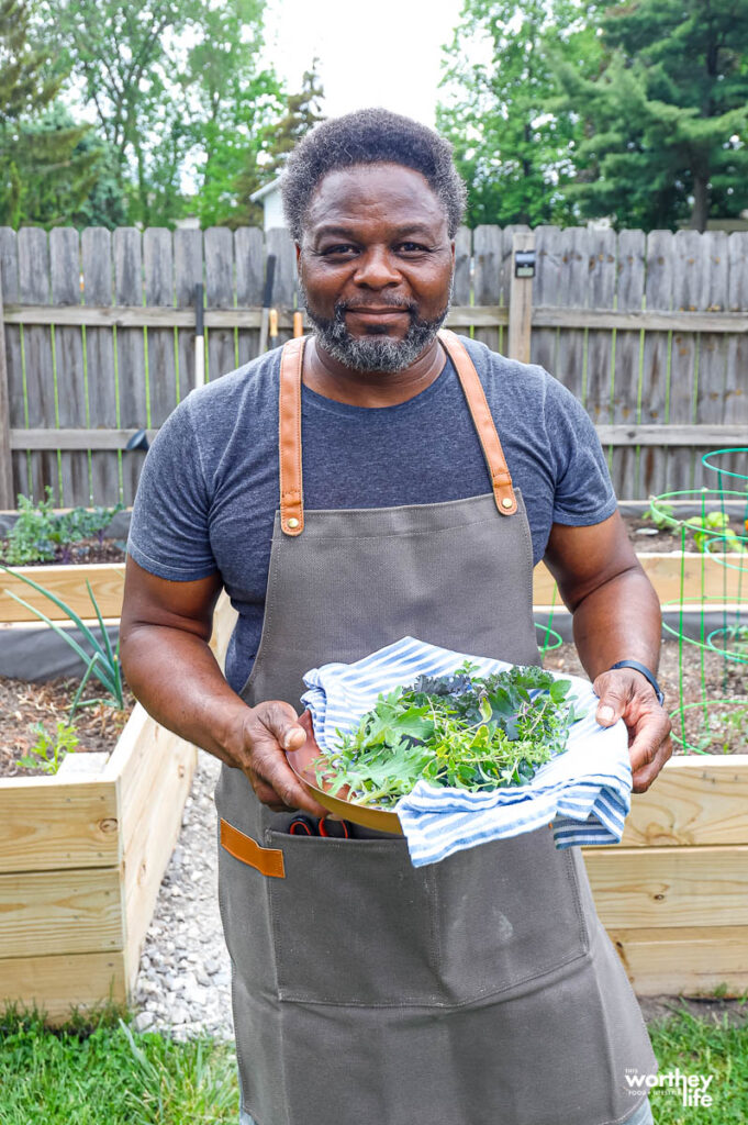a man wearing an apron holding up a platter of fresh herbs