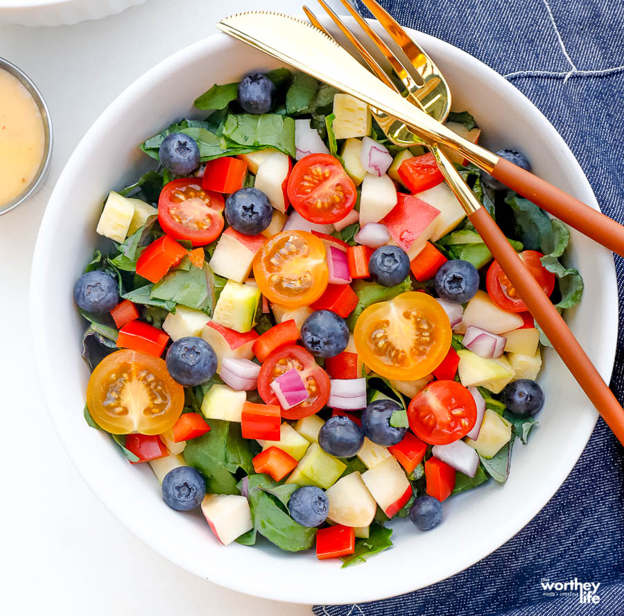 fresh, ripe salad greens with sweet juicy fruits like blueberries and apples mixed in a salad bowl