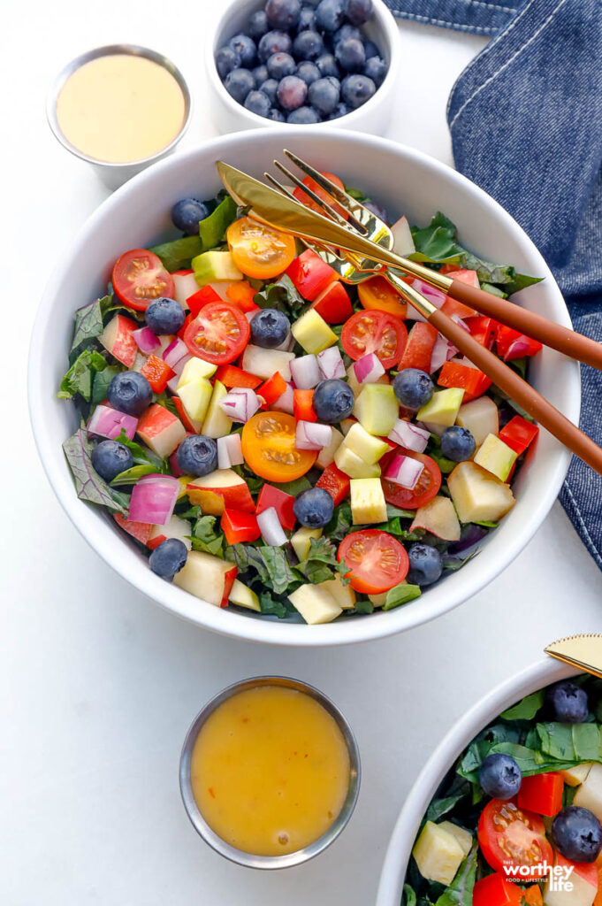 chopped super green salad in a white bowl with a fork and knife