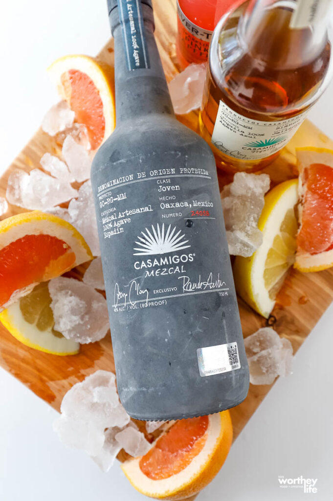 a bottle of mezcal surrounded by sliced paloma fruits