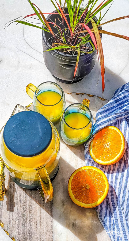 glasses of 100% orange juice in a cup and pitcher