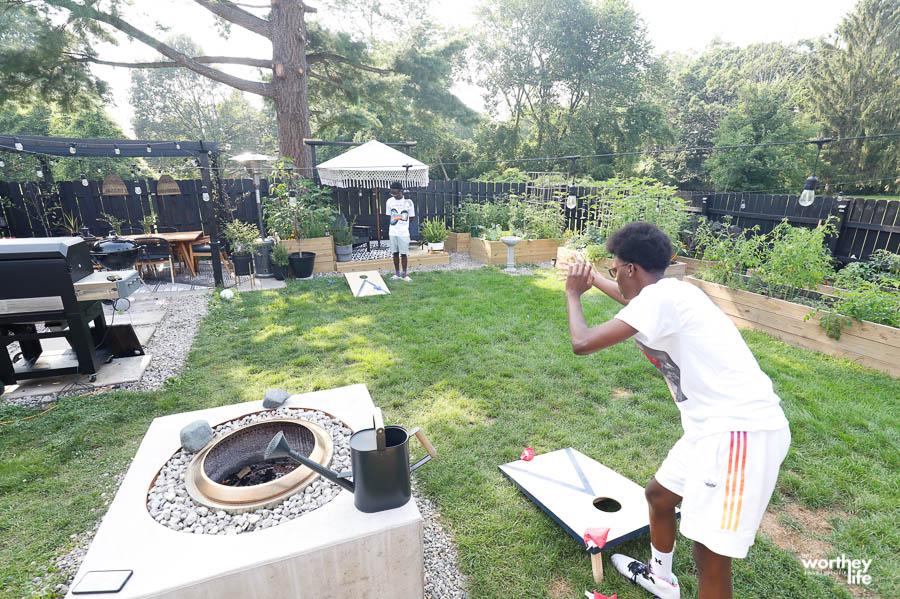 teens playing cornhole in the backyard