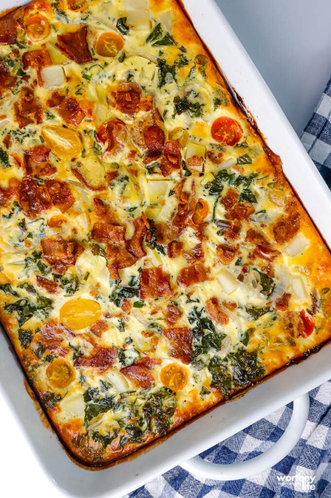 quiche with a crust baked in a white baking dish