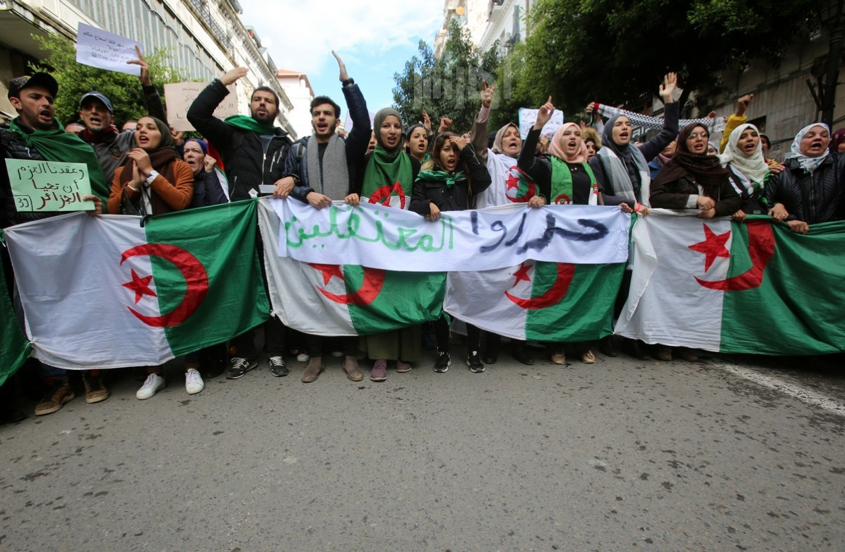 Demonstrators carry national flags during a protest in Algiers